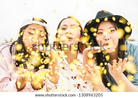 Happy Asian friends doing party throwing confetti outdoor - Young people having fun celebrating at festival event outside - Friendship, fest, entertainment and youth lifestyle concept