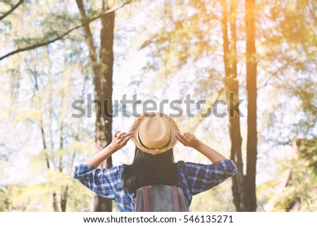 Happy Asian girl backpack in park and forest background, Relax time on holiday concept travel ,color of vintage tone and soft focus