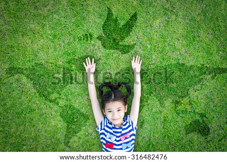 Happy Asian girl child raising hands with happiness lying peacefully w/ dove birds sign/ symbol & world map eco bio green grass: Peaceful mind kid in beautiful & clean love environment: csr concept