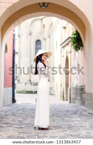 Happy asian girl dressed in traditional Ao Dai white dress with vietnamese conical hat Non La, Leaf Hat. Asian girl walks on the street at cityspace background.