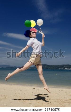 happy asian girl holding balloon at the beach,Phuket Thailand