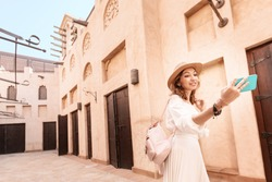 Happy asian girl in white dress taking selfie against narrow streets of old Arabian town in Dubai. Travel destinations and tourism in UAE concept