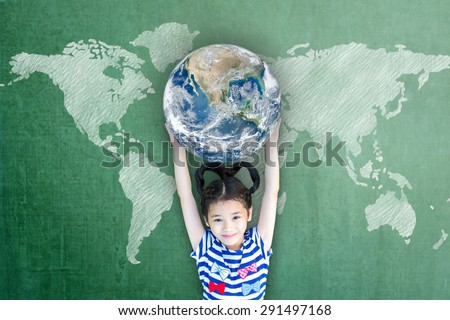 Happy Asian girl kid child raising hands holding globe on green chalkboard with world map background: Children\'s education for world literacy day concept : Elements of this image furnished by NASA