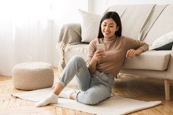 Happy Asian Girl Messaging on Phone at Home, Sitting on Floor near Sofa