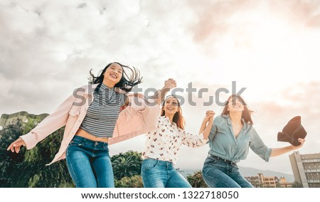 Happy asian girls having fun jumping outdoor at park - Young women friends sharing time together on college break at university campus - Friendship concept with millennial generation - Pastel filter