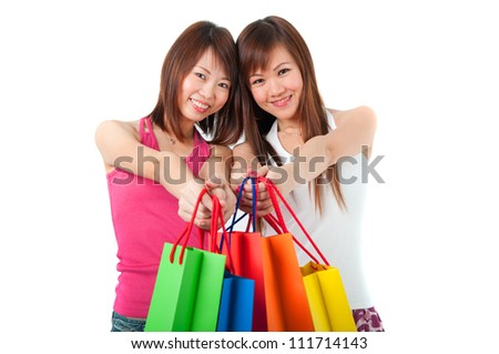 Happy Asian girls standing in shopping bags