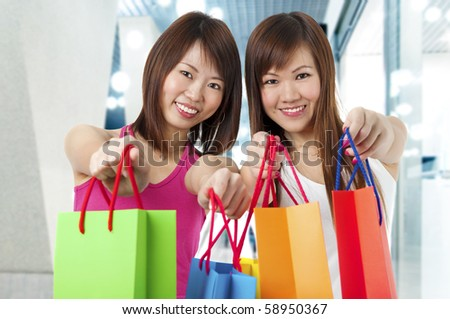 Happy Asian girls standing with shopping bags, shopping mall as background.