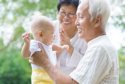 Happy Asian grandparents playing with baby grandchild at outdoor garden.