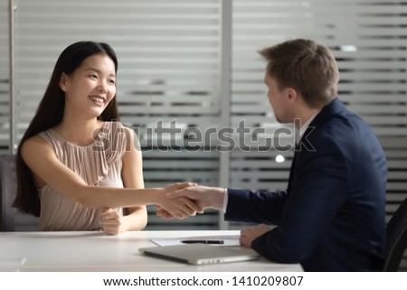 Happy asian job applicant manager handshake hr customer get hired employed at interview make business deal, korean businesswoman shake hand of male client, recruit, human resource, employment concept