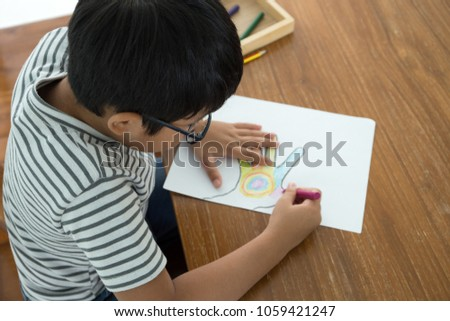 Happy Asian Kid Sit On The Wood Chair And Enjoy Painting Colorful Hand With Crayon Color