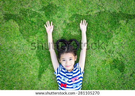 Happy Asian kid with heart-shaped hair raising hands up lying on green grass floor with world map background : World earth day with happy little kid : Save the planet and healthy environment concept