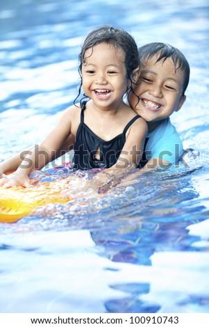 Happy Asian kids having fun at swimming pool during summer