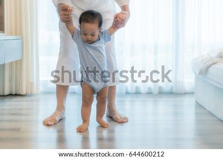 Happy Asian little baby boy learning to walk with mother help in bedroom at home. Family, child, childhood and parenthood concept