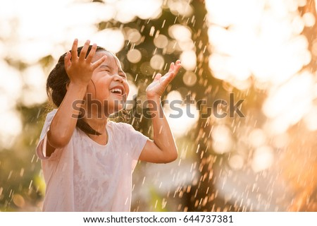 Happy asian little child girl having fun to play with the rain in the evening sunlight in vintage color tone #644737381