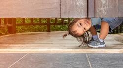 Happy Asian little child girl plays peekaboo under the wooden door in the garden.