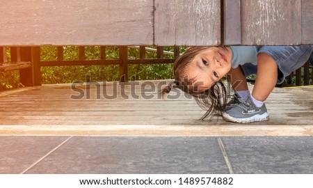 Happy Asian little child girl plays peekaboo under the wooden door in the garden. Stock photo ©
