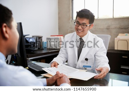 Happy Asian male doctor in consultation with male patient