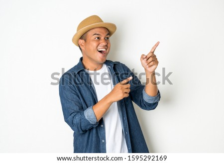 Happy Asian man, aged 30, wears a hat, wears a jean shirt, stands, pointing to an empty space.