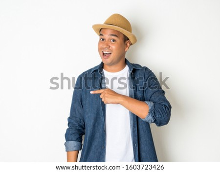Happy Asian man, aged 30, wears a hat, wears a jean shirt, stands, pointing, to an empty space.