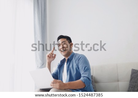 Happy Asian man in blue shirt using laptop at home.