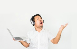 Happy asian man listens to music with headphone funny and dance stay at home.Man worship online in sunday service.Praise the LORD and Worship god at home.Online Church.Christianity lifestyle at home.