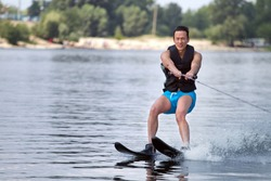 Happy asian man riding water skis on lake in summer