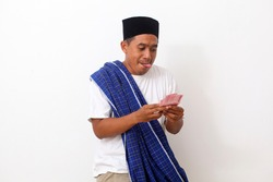 Happy asian man while holding a indonesian money. Isolated on white. Ramadan concept