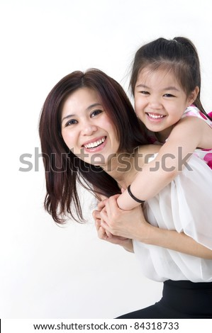 happy asian mother giving her daughter a piggyback ride