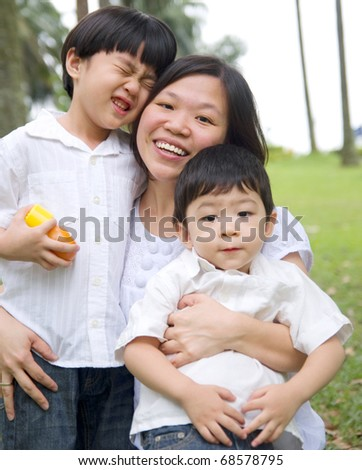 happy asian mother having outdoor fun with sons