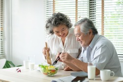 Happy Asian Older couple relaxing preparing and cooking healthy salad at home together. Romantic Senior man and woman smiling enjoying a meal.