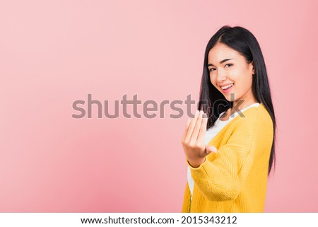 Happy Asian portrait beautiful cute young woman teen smile positive friendly making gesture hand inviting to come here with hand look to camera studio shot isolated on pink background with copy space Сток-фото ©