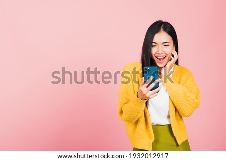Happy Asian portrait beautiful cute young woman teen smiling excited using smart mobile phone studio shot isolated on pink background, Thai female surprised making winner gesture on smartphone