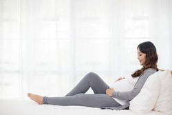 Happy Asian pregnant woman sitting in bed at home bedroom and looking at her bare belly, pregnancy, People and maternity concept