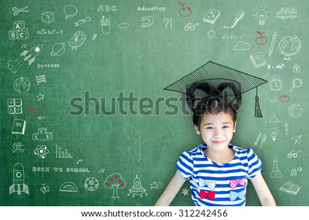 Happy Asian school child girl with big graduation cap/ hat on green color chalkboard background with freehand daydreaming doodle and blank copy space: Smiling female little kid on writable blackboard