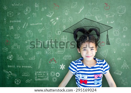 Happy Asian school child girl with heart shaped hair on green color chalkboard background with freehand daydreaming doodle: Smiling female little kid on writable cement concrete backdrop with drawing