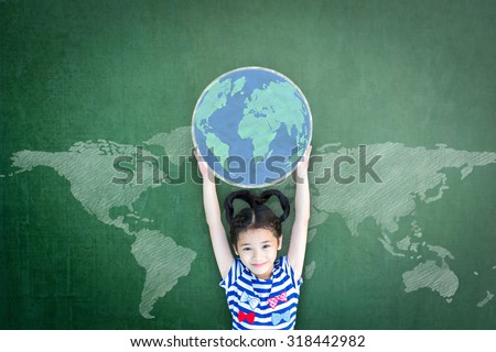 Happy Asian school girl kid child raising hands holding globe on green chalkboard with global world map background & empty copy space for adding texts: Child\'s education for world literacy day concept