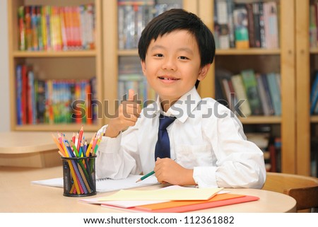Happy Asian schoolboy wearing white shirt and tie sitting at desk gesturing thumbs up