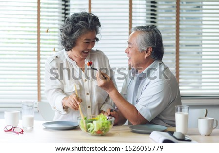 Happy Asian senior couple doing salad in kitchen at house together. Smiling Japanese Elderly man and woman eating healthy food on morning. Romantic Lover, Retirement of Grandfather and Grandmother