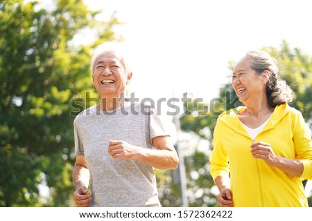 happy asian senior couple running exercising outdoors in park Stockfoto ©