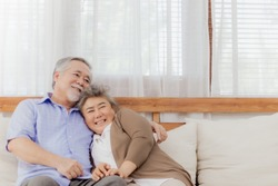 Happy Asian senior couple stay together on sofa at home in romantic moment. Retired lovely elderly smiling grandparent lover hugging, embracing with love and holding hands. Retirement life of older