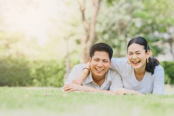 Happy Asian smiling couple in love relaxing on green grass. couple Lying on grass outdoor