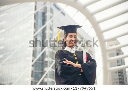 Happy Asian student woman graduate diploma and MBA degree in asian college.Woman holding certificate and wearing hat.Graduate Student and Success Education in University Concept