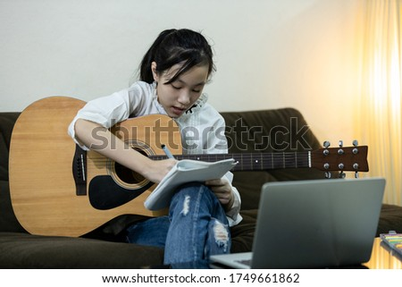 Happy asian teen girl is practicing composing a song,trying to write a new music in diary, female people relaxing time, hobby, lifestyle, inspiration, creative musician enjoy write making up a lyrics Stock photo ©