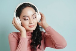 Happy Asian teenage girl listen the music song in wireless headphone from mp3 player technology. relaxation and music lover concept.
