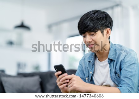 Happy asian teenager using smart phone and smiling on sofa living room at home. Asian man holding and using cellphone for searching data and social media on internet. Teenager and Technology concept.