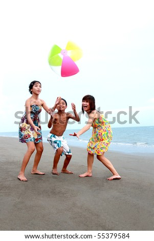 happy asian teenagers playing at the beach - stock photo
