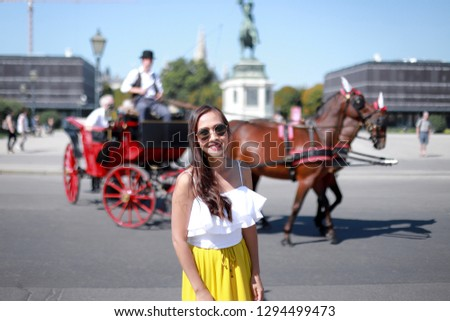 Happy asian tourist woman taking picture with horse carriage famous in Vienna city , Austria around Alte Hofburg Palace on a sunny day in the summer