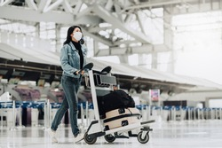 Happy Asian tourist woman with mask protection for coronavirus walking with luggage trolley ready for travel