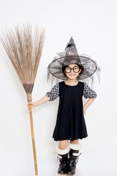 Happy Asian witch child holding magic bloom in Halloween costume