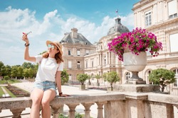 Happy asian woman advertises cheap flights or airlines playing with a small plane against the background of the Luxembourg Palace in Paris